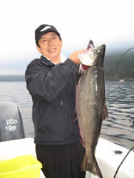 Mr. Kim of Parksville British Columbia shows his 25 pound Chinook that he landed in the Port Alberni Inlet close to China Creek using anchovy.  Doug of slivers Charters Salmon sport fishing was the guide